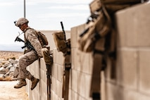 A U.S. Marine with 3rd Battalion, 7th Marine Regiment, 1st Marine Division, scales a wall during counter improvised explosive device training at Marine Corps Air Ground Combat Center, Twentynine Palms, Calif., July 25, 2019. The training was designed to improve the confidence and proficiency in the skill sets Marines and sailors need to operate in an urban environment. (U.S. Marine Corps photo by Lance Cpl. Colton Brownlee)