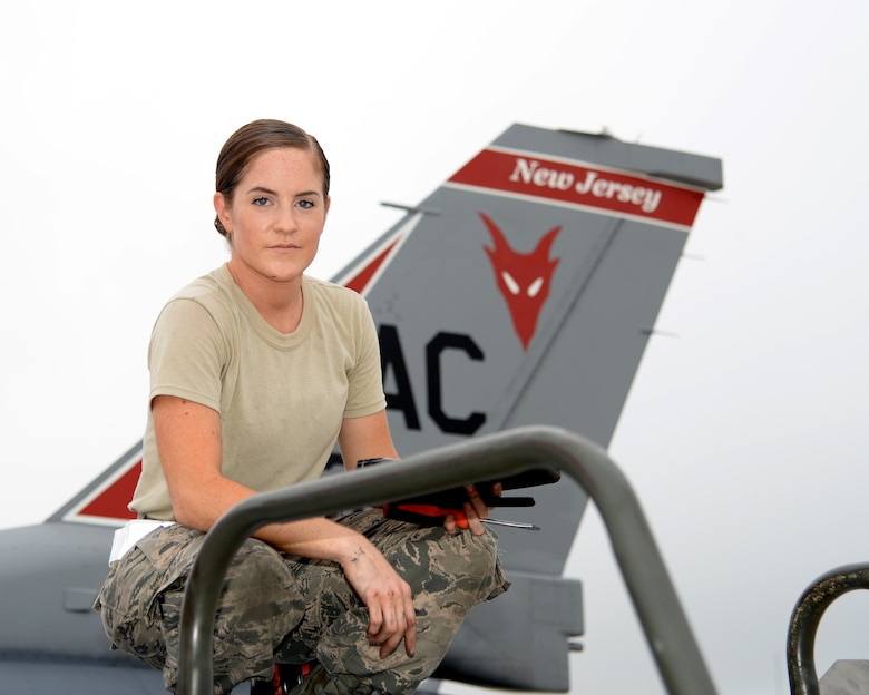 A picture of U.S. Air Force Airman 1st Class Michele Sangillo, crew chief with the New Jersey Air National Guard's 177th Fighter Wing, sitting on the wing of a 177FW F-16C Fighting Falcon.