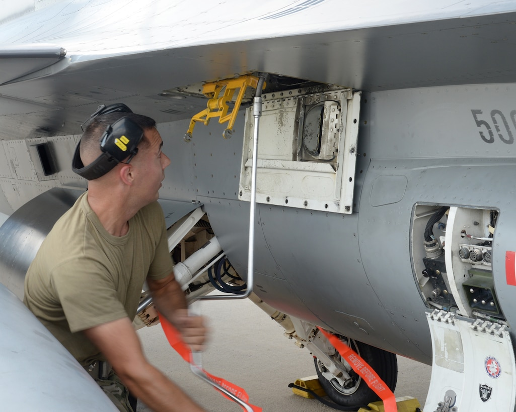 A picture of U.S. Air Force Staff Sgt. Dan Ogburn, weapons loader with the New Jersey Air National Guard's 177th Fighter Wing, working on a 177FW F-16C Fighting Falcon.