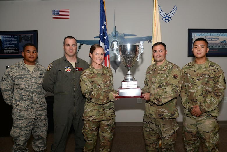 A picture of Airman 1st Class Michele Sangillo and Staff Sgt. Andrew Finnegan holding a combined combat skills champion trophy. Standing to the left of Sangillo is Senior Airman Jonathan Baez and Lt. Col. Matthew Crill. Standing on the right of Finnegan is A1C Jonathan Huynh.