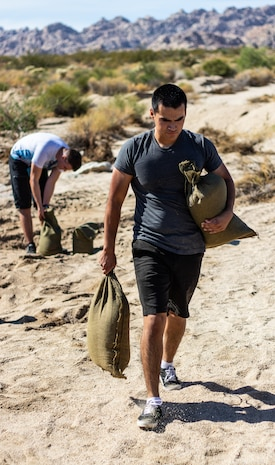 U.S. Marine Pfc. Andy Munoz with 3rd Battalion, 4th Marine Regiment carries sandbags in Twentynine Palms, Calif., July 27, 2019. The Marines and sailors volunteered to assist a veteran and current government service employee with repairing his home after it was damaged by a flash flood. (U.S. Marine Corps photo by Pfc. Shane T. Beaubien)
