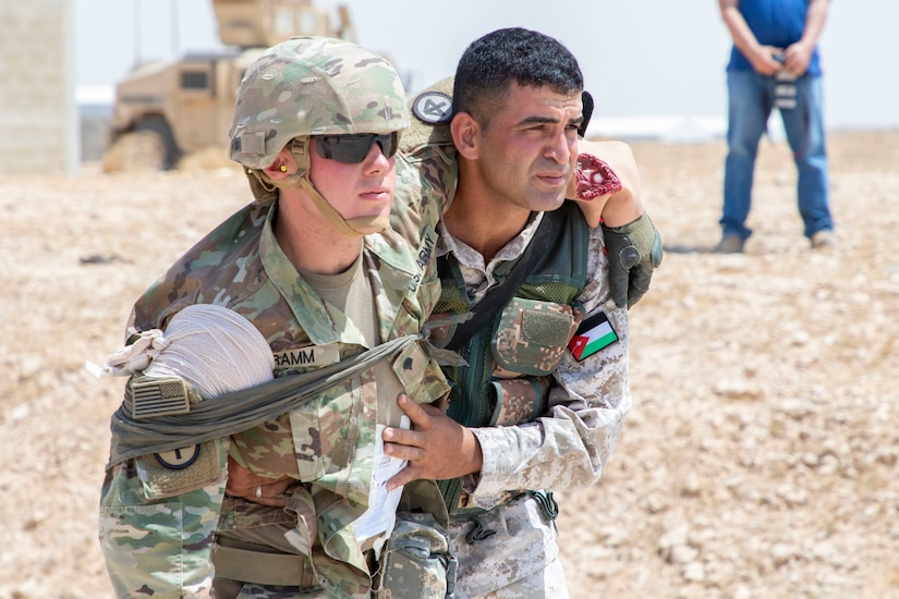 A Jordan Soldier, with 7th Mechanized Battalion, 48th Mechanized Brigade, supports a U.S. Army Soldier, with 1st Squadron, 102nd Cavalry Regiment, 44th Infantry Brigade Combat Team of the 42nd Infantry Division, New Jersey National Guard, mimicking an arm and abdominal injury during medical evacuation training, part of the Jordan Operational Engagement Program at Joint Training Center-Jordan August 27, 2019. The Army is optimizing for interoperability with all our allies and partners to strengthen alliances and deliver more effective coalition operations.