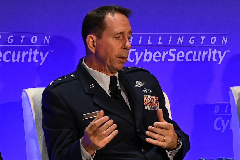 A seated Air Force three-star general gestures while speaking.