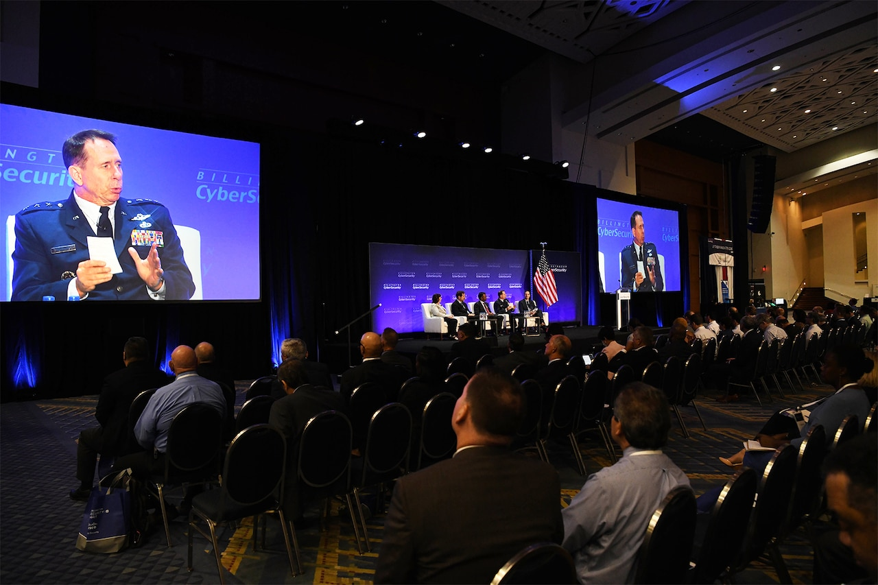 Large screens on each side of a seated panel show an Air Force three-star general panel member speaking.