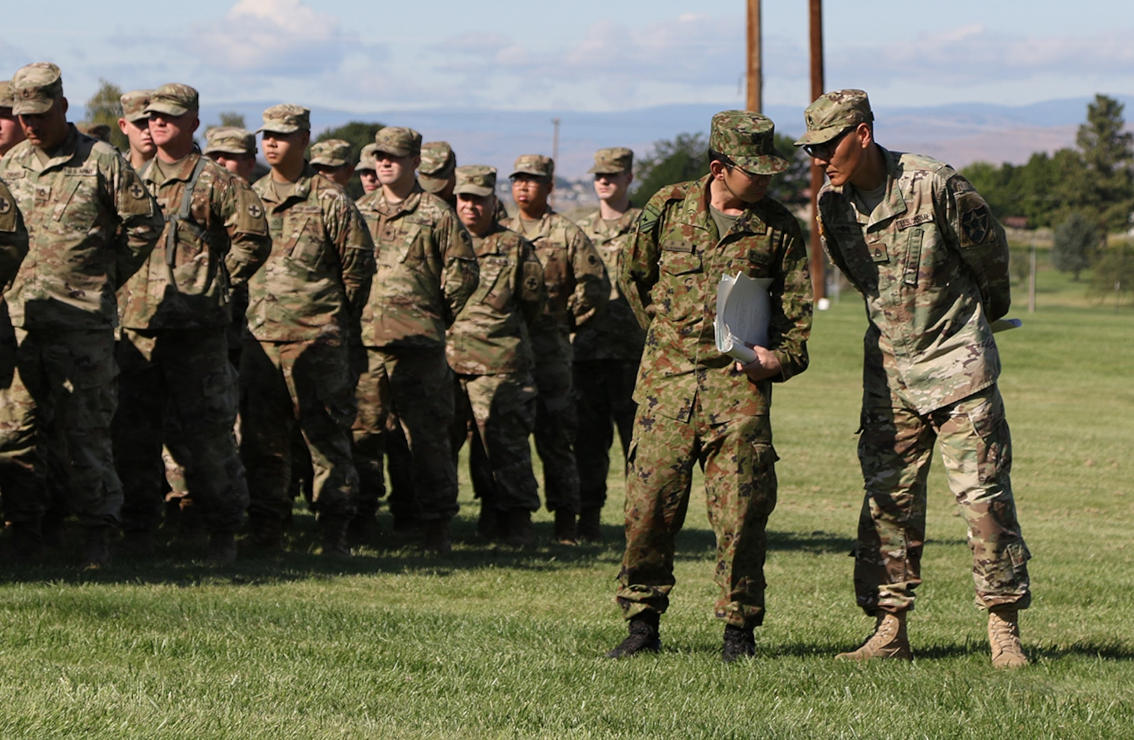 Translators from the Illinois Army National Guard and the Japan Ground Self-Defense Force discuss the Rising Thunder 2019 opening ceremony at Yakima Training Center, Washington, Aug. 30, 2019.