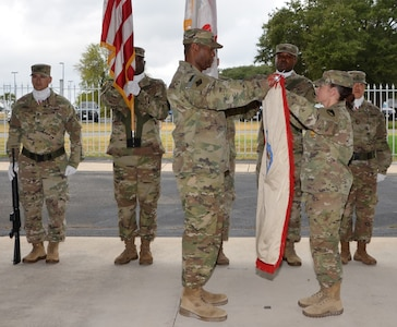 Col. Robert McDonald (left) and Command Sgt. Maj. Sol Nevarezberrios unfurl the 410th Contracting Support Brigade colors during an uncasing ceremony Sept. 5 at Joint Base San Antonio-Fort Sam Houston following the unit's return from a nine-month deployment to Afghanistan. McDonald is the 410th CSB commander and Nevarezberrios is the brigade command sergeant major.