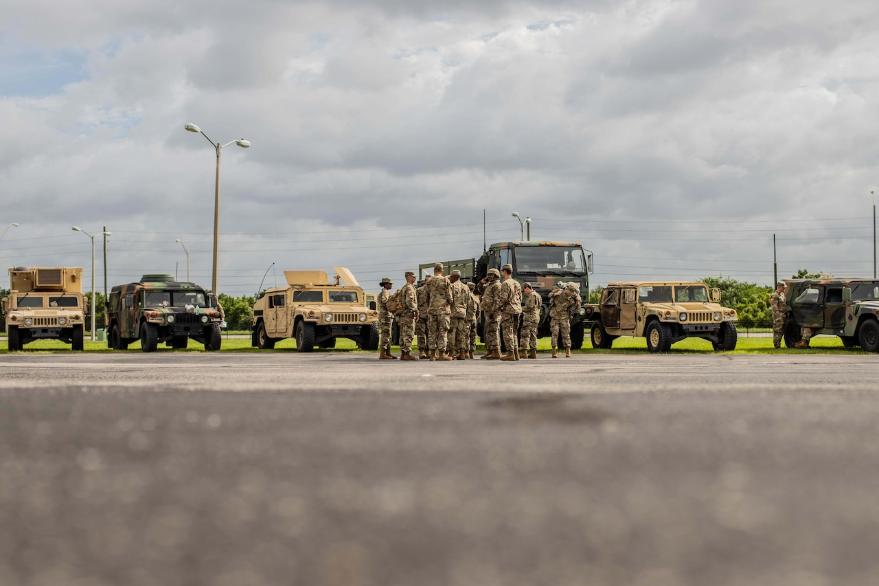 Soldiers stand in front of vehicles.