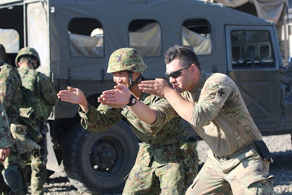 Pfc. Darian Matos  and a Japanese infantryman mimic a rifle stance with their hands, as soldiers watch, Sep. 2, while on Range 15 at Yakima Training Center, during exercise Rising Thunder 19.
