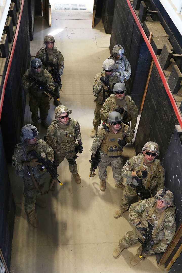 Soldiers from Company D, 2nd Battalion, 130th Infantry Regiment, Illinois Army National Guard, directs attention to a range safety officer as they receive feedback after a room clearance drill during Rising Thunder 19, at Yakima Training Center in Yakima, Washington, Sept. 1, 2019.