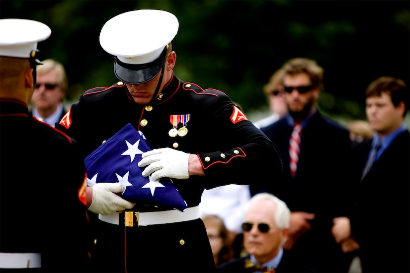 A Marine in dress uniform handles a folded U.S. flag with care as funeral attendees look on in the background.