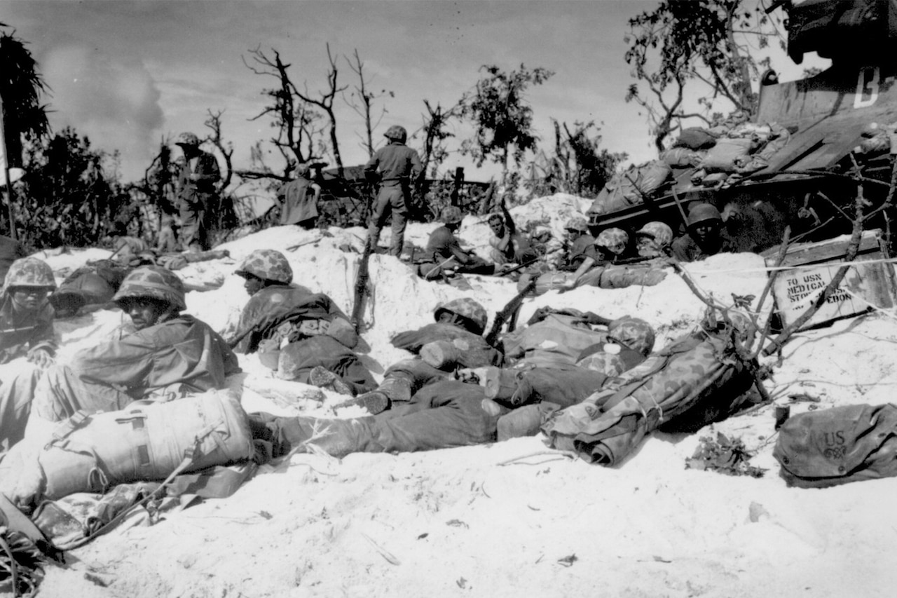 Several Marines in combat dress lay low on a sandy beach with bombed-out trees in the background.