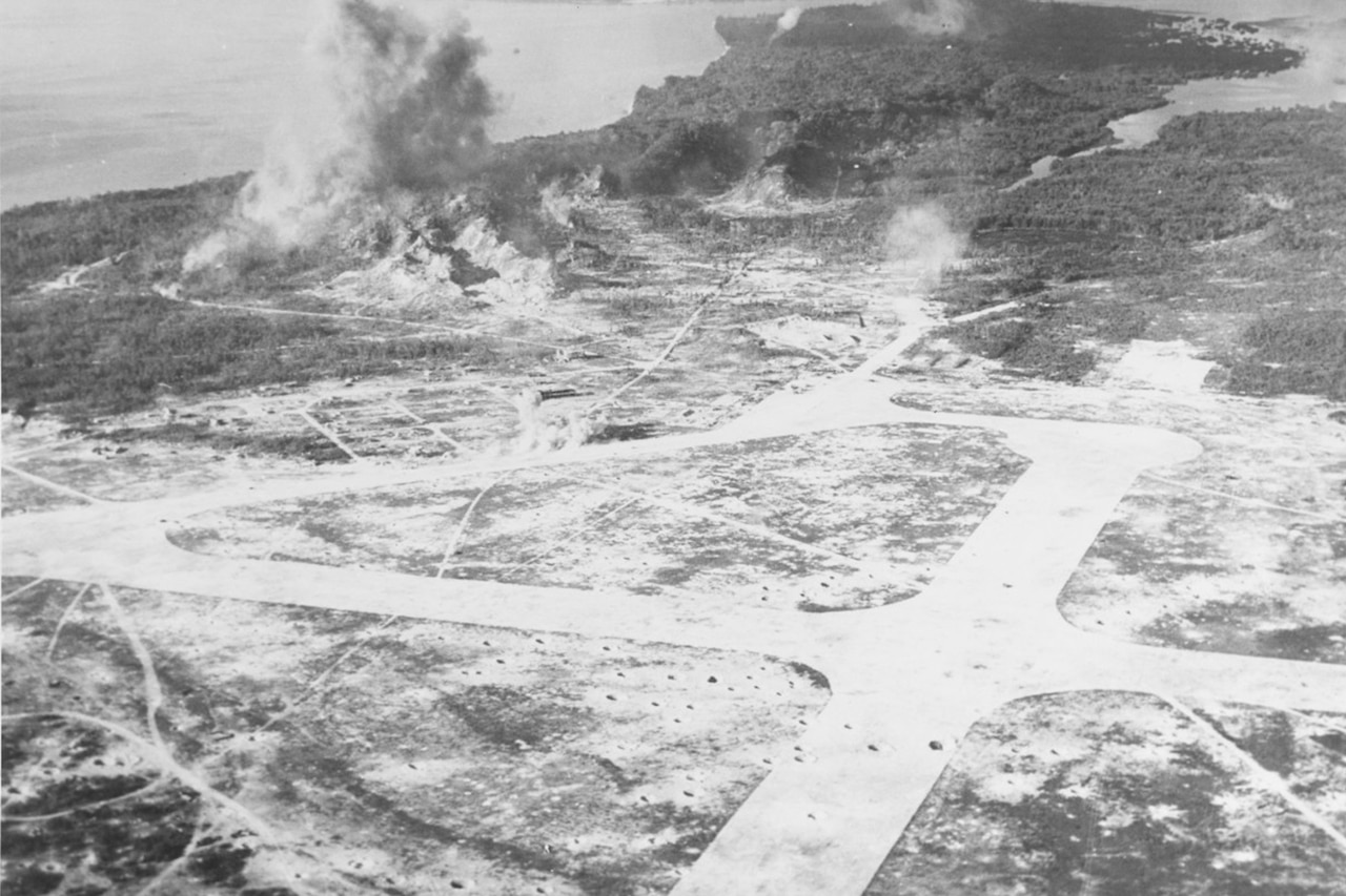 An aerial view of a small island in which bombs can be seen blowing up behind an airfield and near heavily wooded ridges.