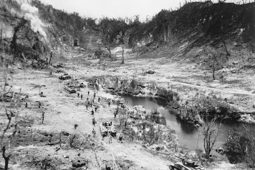 Men and tanks move toward a bombed-out ridge. A small lake is to their right.
