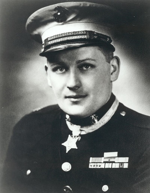 A Marine Corps major in full dress uniform wears the Medal of Honor around his neck.