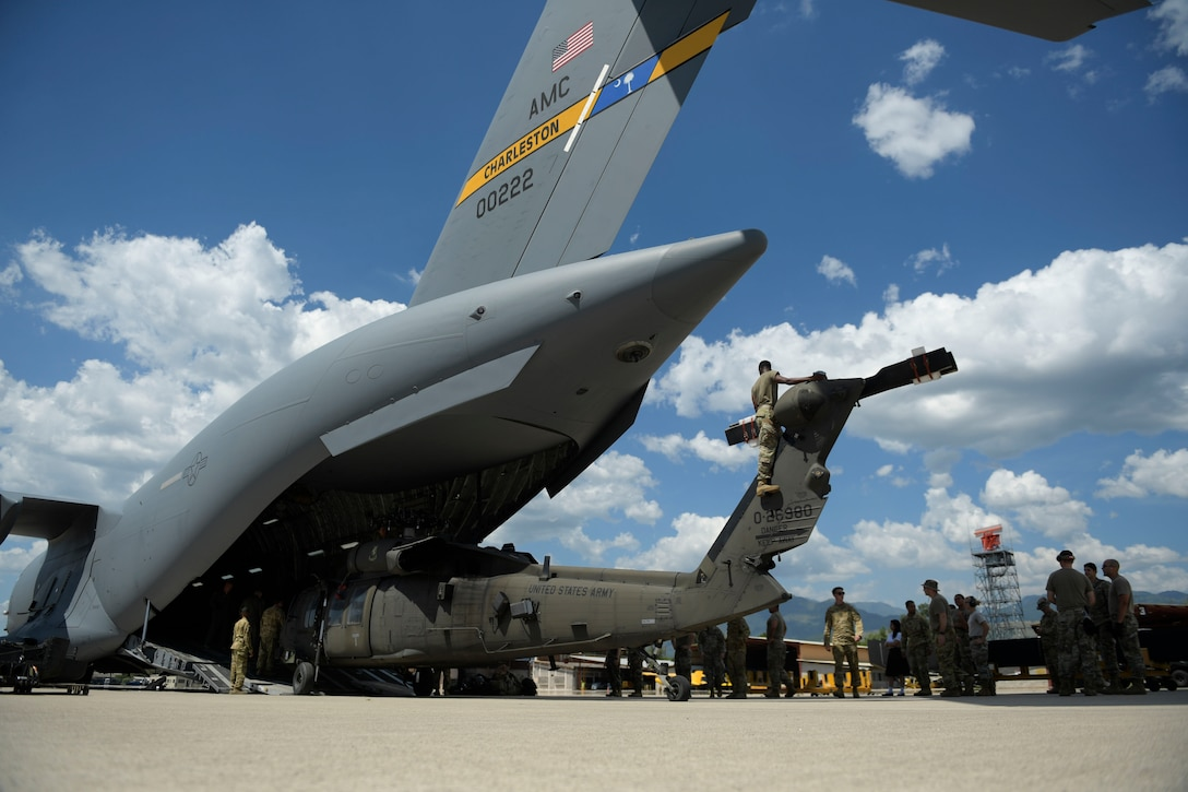 Military personnel remove a damaged military helicopter through the tailgate of a large transport jet.