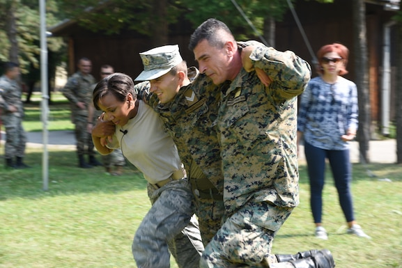 Tech. Sgt. Patricia Medina, medical administrator, 175th Medical Group, Maryland Air National Guard performs a SEAL Team Three carry with members of the Armed Forces of Bosnia-Herzegovina, during a medical training exercise August 26, 2019, Banja Luka, Bosnia. Throughout the training, soldiers of the Armed Forces of Bosnia-Herzegovina received classroom instruction in addition to hands-on tactical combat casualty care application training. (U.S. Air National Guard photo by Staff Sgt. Enjoli Saunders)