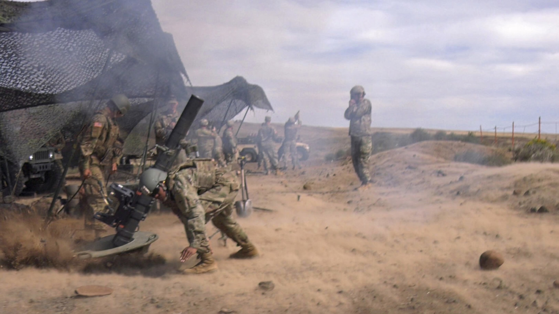 Soldiers from Headquarters and Headquarters Company, 2nd Battalion, 130th Infantry Regiment, based in Marion, Illinois, crouch as the concussion of a 120mm mortar tube kicks up dirt during Rising Thunder 19.