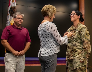 Newly promoted Sgt. 1st Class Erin Connelly's sister, Candy Jansen, places Connelly's new rank on her uniform during a promotion ceremony Sept. 4