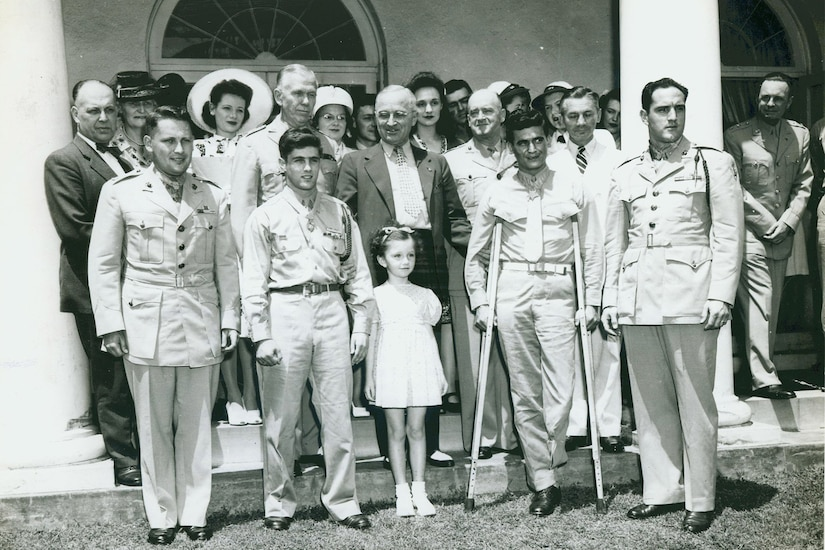 A group, including four service members wearing Medals of Honor, stands on a lawn with President Harry S. Truman and their families.