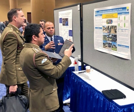 """Lt. Col. Luis Berrios, 433rd Aeromedical Staging Squadron chief nurse and 433rd Medical Group chief of education and training, speaks to an Australian Army major and captain, about his quality improvement project titled """"Addressing Reserve Joint-Service Medical Training Gaps through Multi-Faceted Expeditionary Simulation"""" at the 2019 Military Health System Research Symposium, Aug. 20, 2019 in Kissimmee, Florida."""