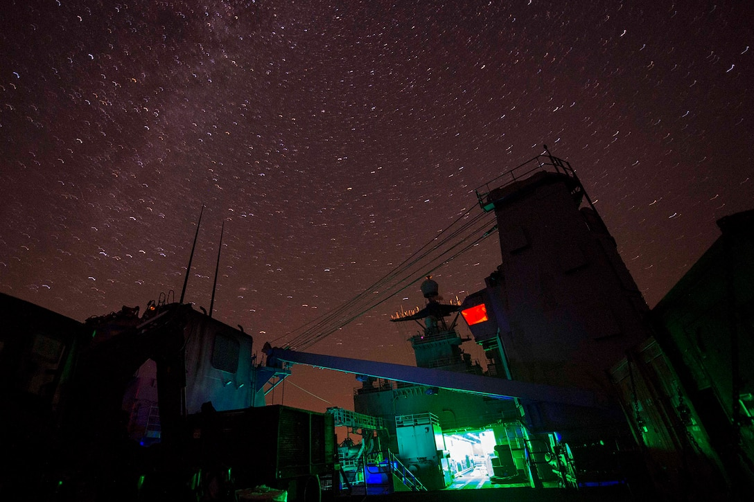 A ship transits a body of water at night.