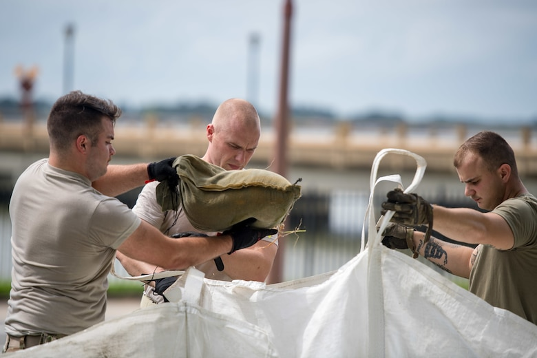 Airmen move sandbags in preparation for Hurricane Dorian