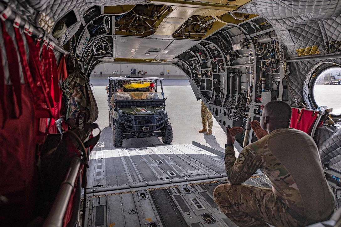 A service member sitting in an open aircraft motions to a vehicle on a flightline.