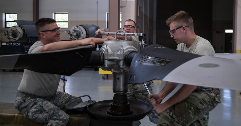 Tech. Sgt. Steve Lew (left), an aerospace propulsion technician, Master Sgt. Shawn Froehling (middle), a flight chief, and Senior Airman Sean Kenny (right), an aerospace propulsion technician, all assigned to the 910th Maintenance Squadron, are torqueing the bolts as a step in the assembly procedure, Aug. 11, 2019 at Youngstown Air Reserve Station.