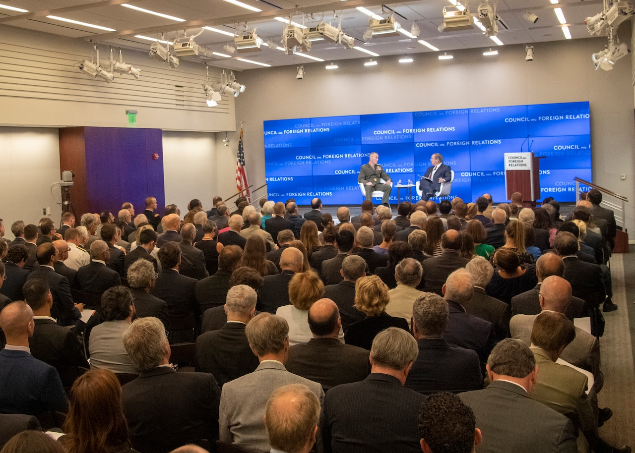 Two men speak on stage.