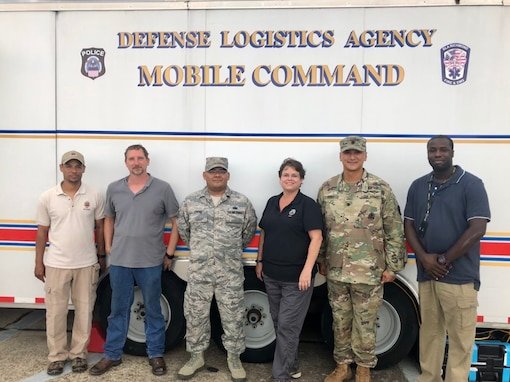 Military and civilian personnel stand in front of a mobile command vehicle