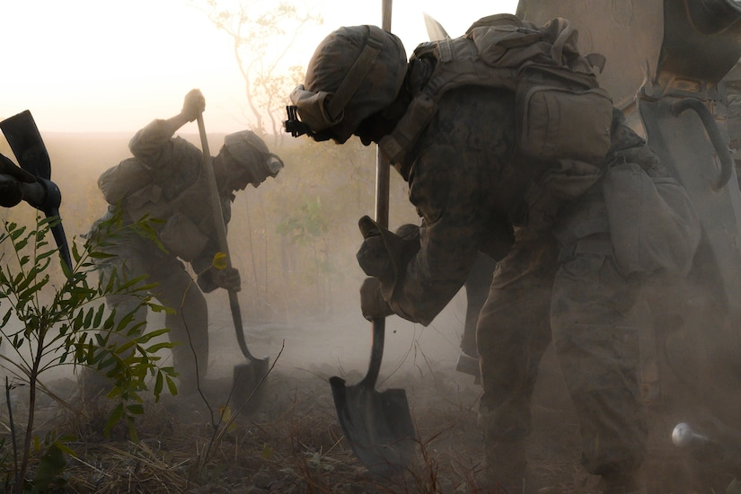 Marines shovel dirt to support a howitzer.