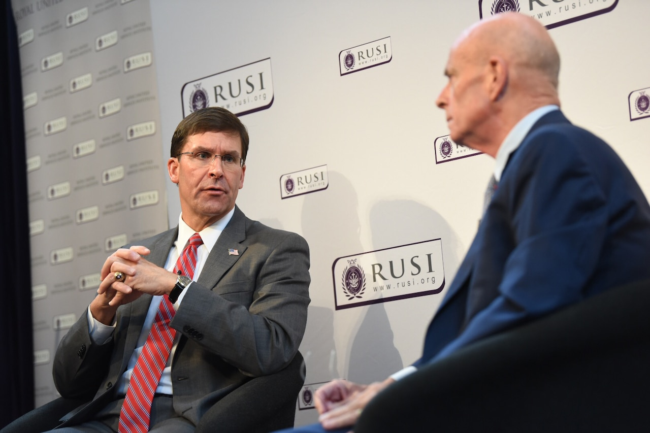 Defense Secretary Dr. Mark T. Esper speaks to another person as both sit on chairs on a stage.