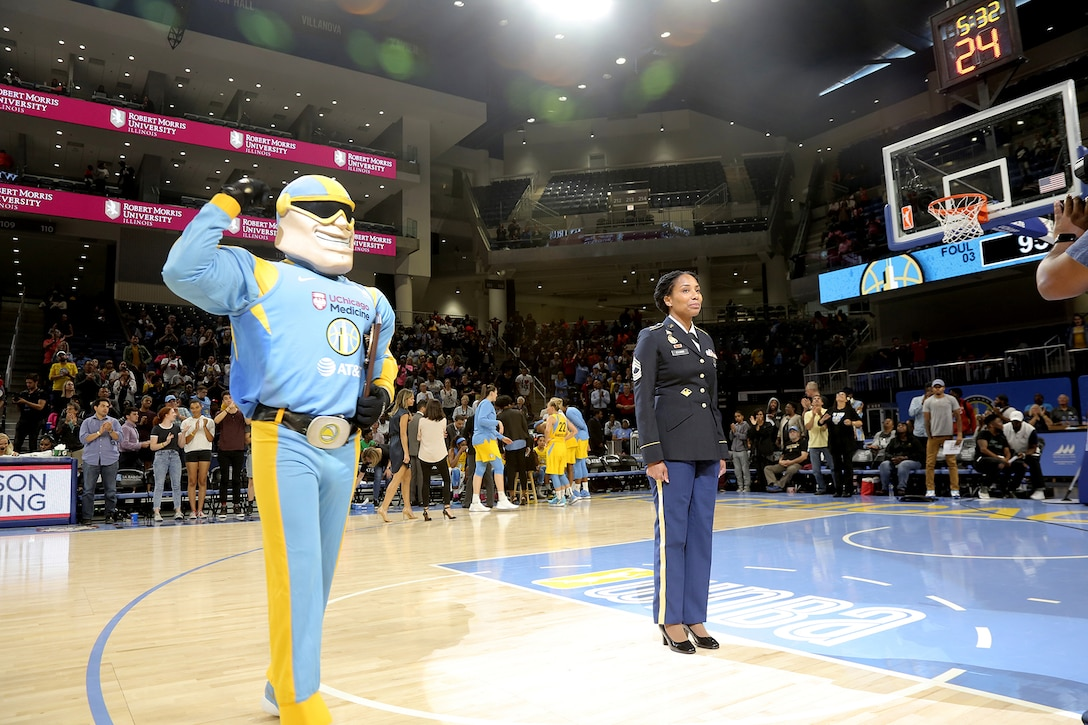 Sky Guy, the Women's National Basketball Association's Chicago Sky team mascot, prepares to present Army Reserve Master Sgt. Ebony Evans a plaque honoring her service during the Chicago Sky's final home game, of the regular season, at the Wintrust Arena in Chicago, Illinois, September 1, 2019.