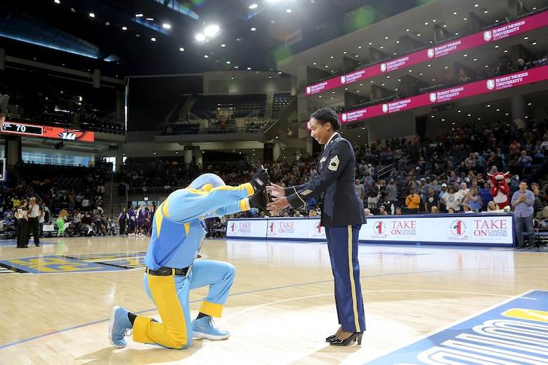 Sky Guy, the Women's National Basketball Association's Chicago Sky team mascot, presents a plaque to U.S. Army Reserve Master Sgt. Ebony Evans in front of thousands of spectators, honoring her service during the Chicago Sky's final home game, of the regular season, at the Wintrust Arena in Chicago, Illinois, September 1, 2019.