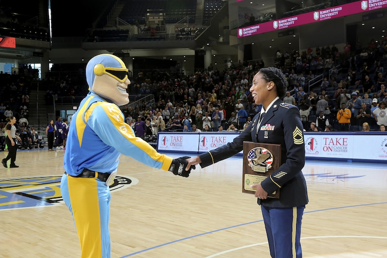 Sky Guy, the Women's National Basketball Association's Chicago Sky team mascot, shakes hands with U.S. Army Reserve Master Sgt. Ebony Evans after honoring her for her service during the Chicago Sky's final home game, of the regular season, at the Wintrust Arena in Chicago, Illinois, September 1, 2019.