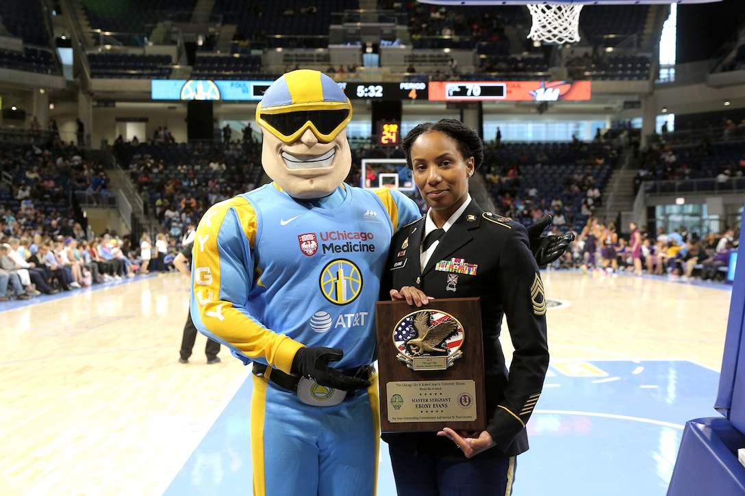 Sky Guy, left, the Women's National Basketball Association's Chicago Sky team mascot, and U.S. Army Reserve Master Sgt. Ebony Evans pause for a photo after she receives an honor for her service during the Chicago Sky's final home game, of the regular season, at the Wintrust Arena in Chicago, Illinois, September 1, 2019.