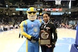 Sky Guy, left, the Women's National Basketball Association's Chicago Sky team mascot, and U.S. Army Reserve Master Sgt. Ebony Evans pause for a photo after she receives an honor for her service during the Chicago Sky's final home game, of the regular season, at the Wintrust Arena in Chicago, Illinois, September 1, 2019. Evans was honored during the game for her 19 years of service in the Army to include two deployments in support of Operation Iraqi Freedom and Operation Noble Eagle.