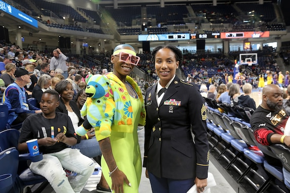 U.S. Army Reserve Master Sgt. Ebony Evans, right, pauses for a photo with a game spectator after she received an honor for her service during the Chicago Sky's final home game, of the regular season, at the Wintrust Arena in Chicago, Illinois, September 1, 2019.