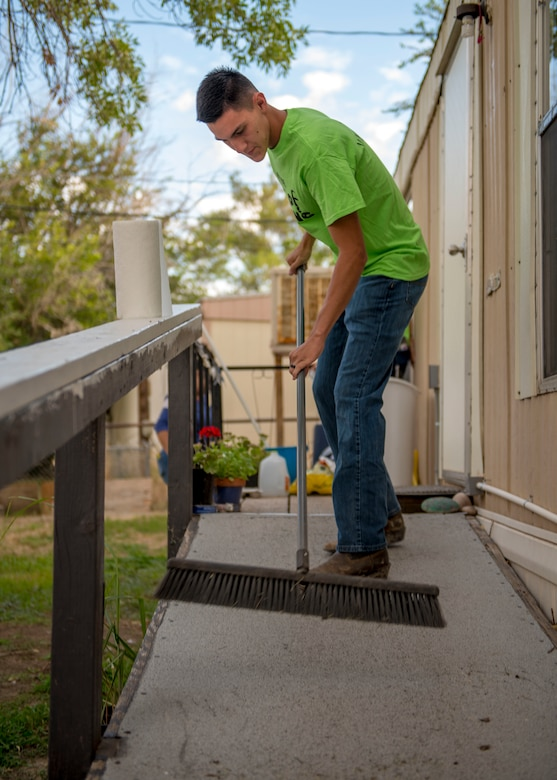 Airman 1st Class Jacob Boren, 9th Aircraft Maintenance Squadron MQ-9 Reaper weapons load crew member, sweeps a porch, Sept. 6, 2019, at a residence in Alamogordo, N.M. Day of Caring volunteers performed various tasks, such as home repairs and yard work, at pre-determined job sites for individuals who are either unable to accomplish the tasks themselves or do not the resources to do so. (U.S. Air Force photo by Airman 1st Class Kindra Stewart)