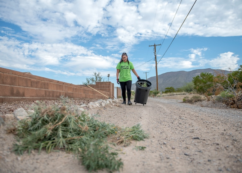 Tarah Martinez, a local community volunteer, throws away weeds, Sept. 6, 2019, at a residence in Alamogordo, N.M. Day of Caring volunteers performed various tasks, such as home repairs and yard work, at pre-determined job sites for individuals who are either unable to accomplish the tasks themselves or do not the resources to do so. (U.S. Air Force photo by Airman 1st Class Kindra Stewart)