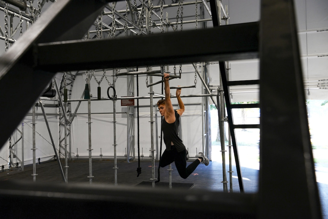 Second Lt. Michelle Strickland, 37th Flying Training Squadron student pilot, swings across monkey bars, Sept. 4, 2019, on Columbus Air Force Base, Miss. Strickland has been practicing on the Alpha Warrior rig to prepare for the upcoming 2019 Inter Service Alpha Warrior Final Battle competition at Retama Park in Selma, Texas, Sept. 12 and 14. (U.S. Air Force photo by Airman 1st Class Jake Jacobsen)