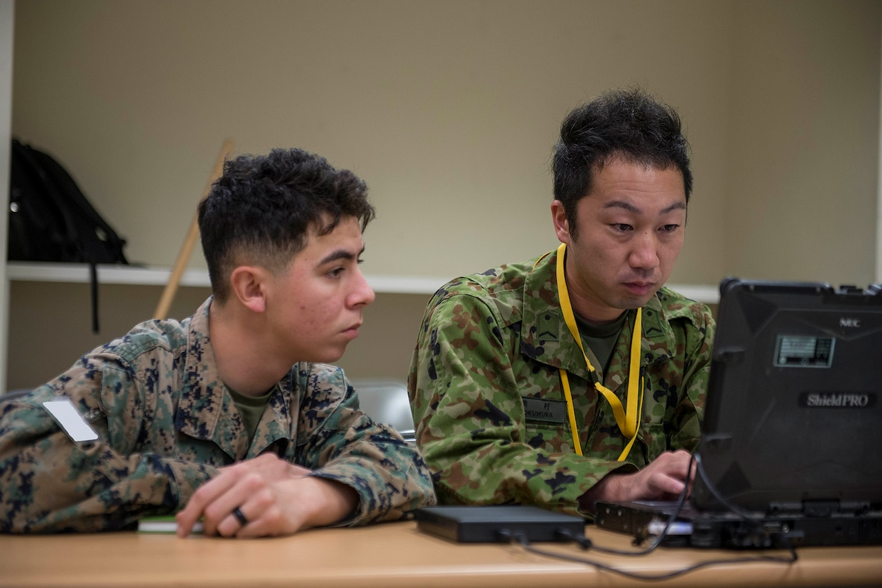 Two men in camouflage uniforms sit in front of a laptop.