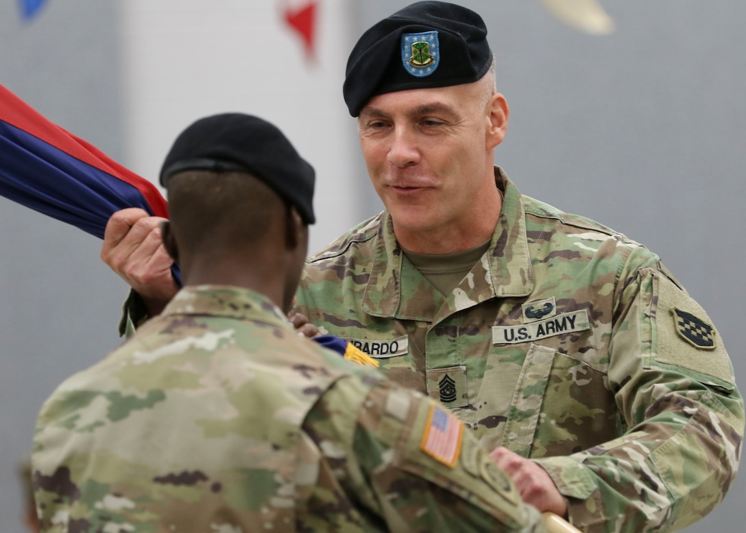 Command Sgt. Maj Andrew Lombardo, the outgoing command sergeant major for the U.S. Army Reserve's 99th Readiness Division, receives the colors from 1st Sgt. Earl Morgan, the 99th Readiness Division Headquarters and Headquarters Company first sergeant, during a change of responsibility ceremony Sept. 7, 2019. The change of responsibility is a transition that is rich with symbolism and heritage, and serves the dual function of recognizing the enlisted service of the departing command sergeant major, and providing official recognition of the change of responsibility as senior noncommissioned officer to the incoming command sergeant major. (U.S. Army Reserve Photo by Sgt. Bethany L. Huff)