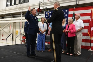 Maj. Gen. Al Dohrmann, the North Dakota adjutant general, right, swears in Brig. Gen. Robert Schulte, to his promoted rank of brigadier general at the North Dakota Air National Guard Base, Fargo, N.D., Sept. 7, 2019, as his family, and unit members look on. Schulte will assume duties as the North Dakota National Guard Joint Force Headquarters Chief of Staff for Air.