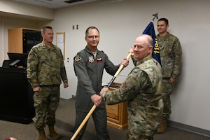 Col. Bryan Delage, the North Dakota National Guard state air surgeon, right, hands the command flag to Col. Joseph Wyatt as Wyatt assumes the duties of the 119th Medical Group commander at the North Dakota Air National Guard Base, Fargo, N.D., Sept. 7, 2019.