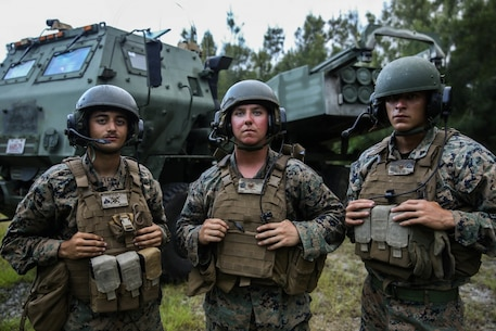 U.S. Marines Cpl. Henry Kijewski IV (left), Sgt. Joshua Luedtke (center), and Cpl. Pablo Villegas (right), with 3rd Battalion, 12th Marine Regiment, 3rd Marine Division, stand in front of a High Mobility Artillery Rocket System, during the Central Training Area HIMARS field training exercise, known as CTA HIMARS, on Camp Hansen, Okinawa, Japan, from Aug. 15-30, 2019.