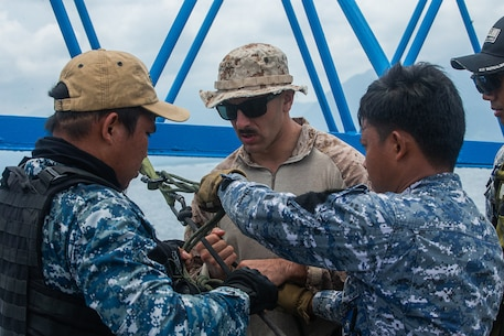 A Marine with the 31st Marine Expeditionary Unit's Maritime Raid Force secures a safety for a hoisting system with members of the Philippine Coast Guard during Baker Piston 19-1, Puerto Princesa, Palawan, Philippines, August 13, 2019. During Baker Piston 19-1, the Marines of the 31st MEU's MRF are exchanging Visit, Board, Search and Seizure techniques and procedures with members of the Philippine National Police Maritime Group and Philippine Coast Guard around the island of Palawan. The 31st MEU, the Marine Corps' only continuously forward-deployed MEU, provides a flexible and lethal force ready to perform a wide range of military operations as the premier crisis response force in the Indo-Pacific region. (Official U.S. Marine Corps photo by Cpl. Isaac Cantrell)