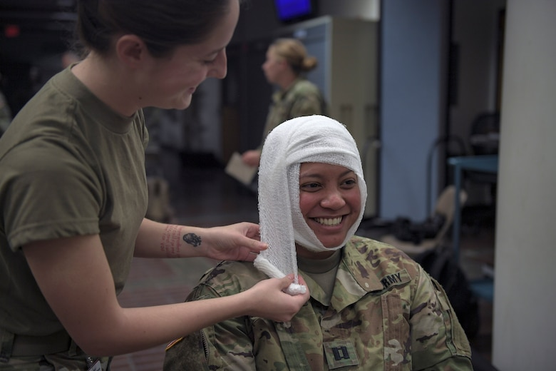 A soldier smiles as an Airman from the 51st Medical Group dresses her head wound during Operation Ascending Eagle, Aug. 28, 2019, at Osan Air Base, Republic of Korea. Air Force and Army medics jointly operated in the simulated large casualty training to enhance their aeromedical evacuation and patient transportation procedures. (U.S. Air Force photo by Staff Sgt. Greg Nash)