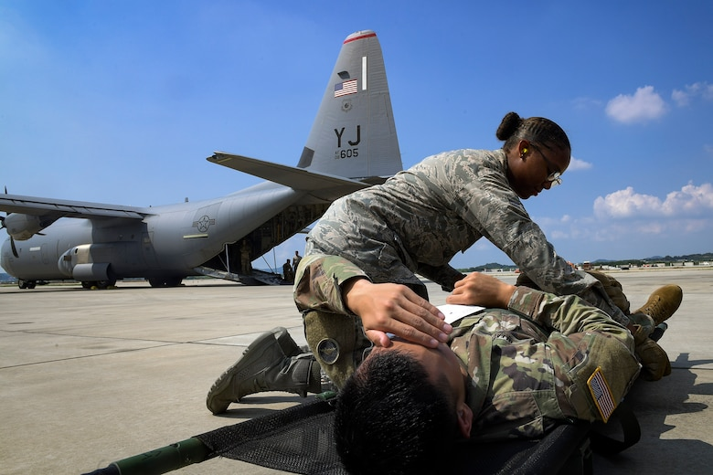 An Airman from the 51st Medical Group helps a soldier recover from injuries during Operation Ascending Eagle, Aug. 28, 2019, at Osan Air Base, Republic of Korea. Air Force and Army medics jointly operated in the simulated large casualty training to enhance their aeromedical evacuation and patient transportation procedures. (U.S. Air Force photo by Staff Sgt. Greg Nash)