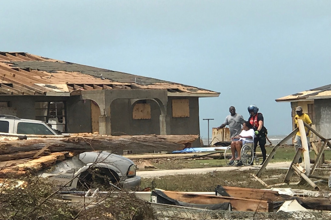 A Coast Guardsman uses a wheelchair to help a group of people evacuate their home in the Bahamas.
